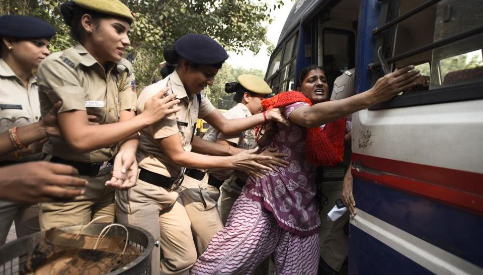 A protestor being detained after civic officials demolished tents and makeshift structures at Jantar Mantar in New Delhi.