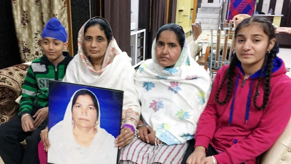Family of Amrik Kaur, who died in 2014, with her photograph at their home in Amarkot, Tarn Taran, on Monday.