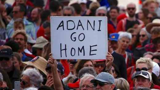 A protester holds a sign as he participates in a national Day of Action against Adani's planned coal mine project in northeast Australia at Bondi Beach last October.