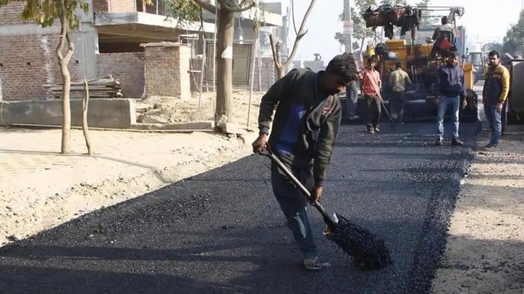 A worker at the construction site of the first plastic road in Gurugram, in 2018.