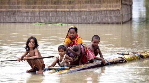 Flood affected people use rafts made of banana trunks to move to safer places at Mayong in Morigaon district of Assam.