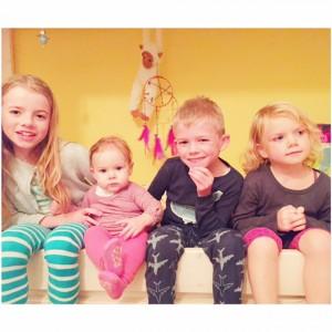 4 kindjes op de rand van het bed