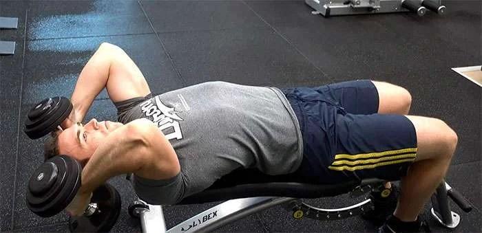 Exercício rosca testa com halteres passando por trás da cabeça