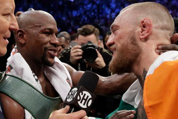 Floyd Mayweather Jr., left, speaks with Conor McGregor after a super welterweight boxing match Saturday, Aug. 26, 2017, in Las Vegas. (AP Photo/Isaac Brekken)