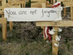 wooden in crosses in field with a note that says you are not forgotten on one