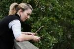 girl holding two twigs over bridge