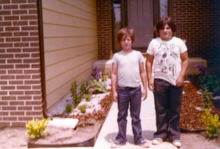 cory fosco and his brother in front of their house's walkway
