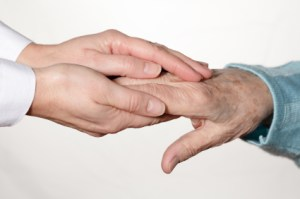 young female hands clasping an older man's hands