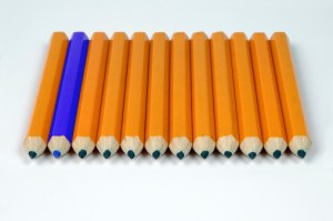 row of yellow pencils with one blue pne