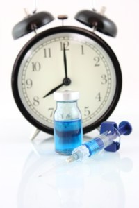 clock with bottle and syringe to signify waiting for a cure