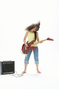 teenage girl playing eletric guitar with amp