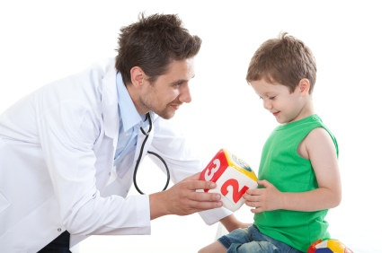 young male pediatrician with boy holding block