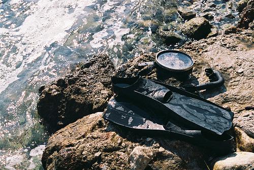snorkeling gear on rock at shore