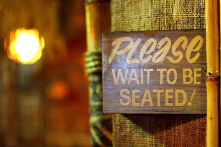 please wait to be seated sign at diner