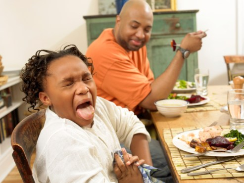 Young Girl Sits at a Table for Lunch With Her Father, Sticking Out Her Tongue in Disgust at the Food