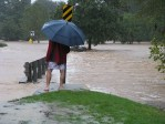 man in umbrella standing in flooding street