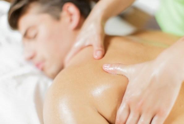 hands on mans shoulders massage table