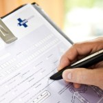 close-up of someone filling out doctor health form