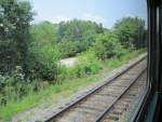 view of train tracks from outside train window - grass and trees