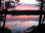 canoe on side of lake, sunset in back