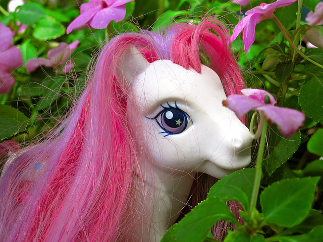 pink my little pony - just head and pink mane showing, against grass and purple flowers