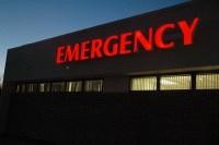 red lit-up emergency sign on hospital exterior
