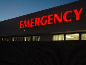 red lit-up emergency sign on hospital exterior