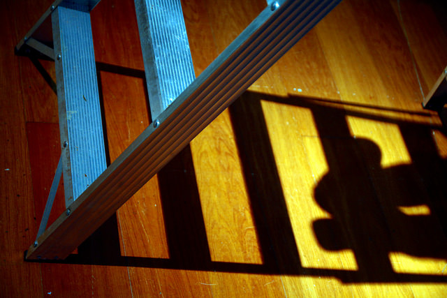 artistic shot of small ladder with shadow of ladder and feet off to side.