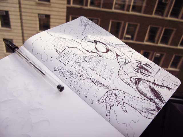 sketch book open to page of spiderman with wrist shooting a web
