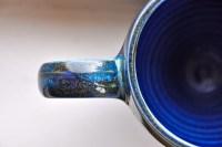 handmade ceramic mug, looking down at handle and half of mug; shiny blues and grees