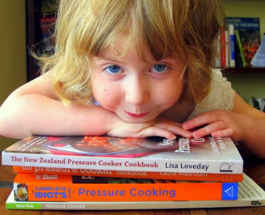 pressure cooker book reviews -ada on a stack of cookbooks