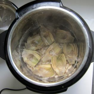 View inside of pressure cooker of artichokes and beans that are cooked.