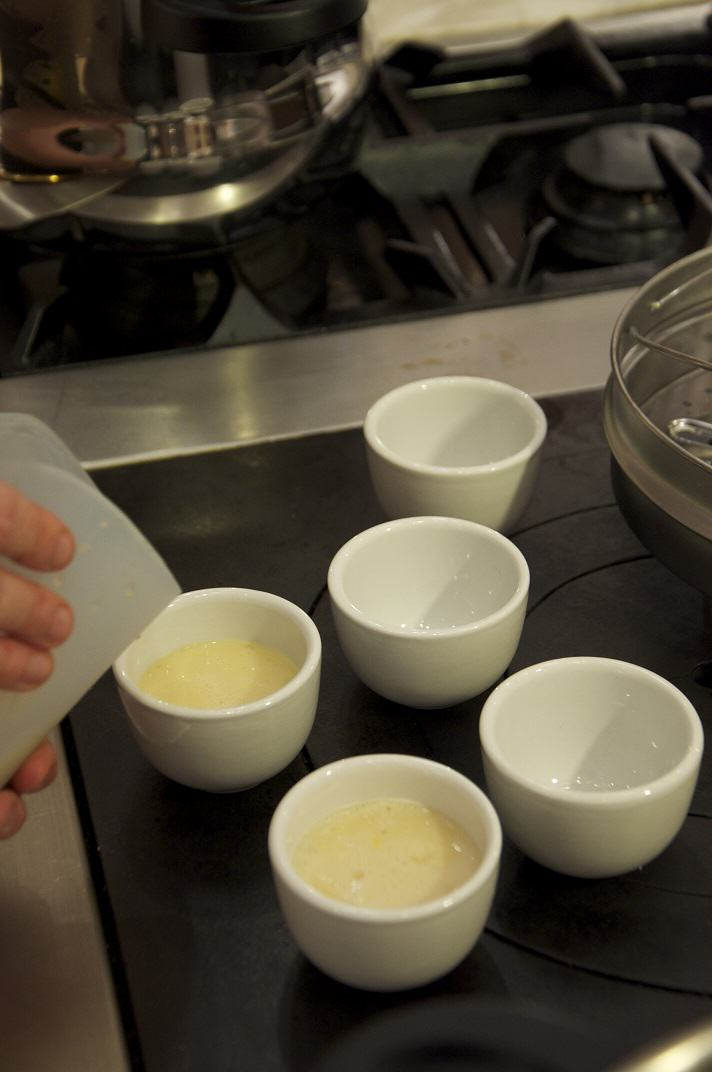 Pouring flans into ramekins (Chinese tea cups).