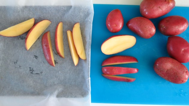 Slice potatoes into wedges and toss into parchment paper-covered cookie sheet.