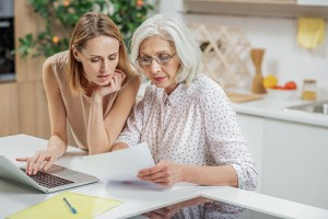 family caregiver helping senior with paperwork