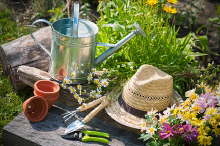 watering can and other garden tools with a straw hat