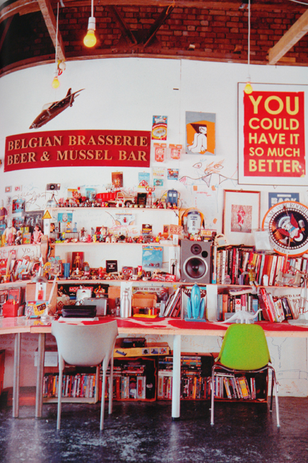 wall of shelves holding books and toys with a red Belgian brasserie sign above