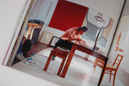man working at a large wooden table with a huge red painting in the background