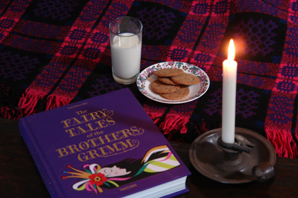 Fairytales of the Brothers Grimm book with glass of milk, plate of cookies and lit candle in a pewter candleholder