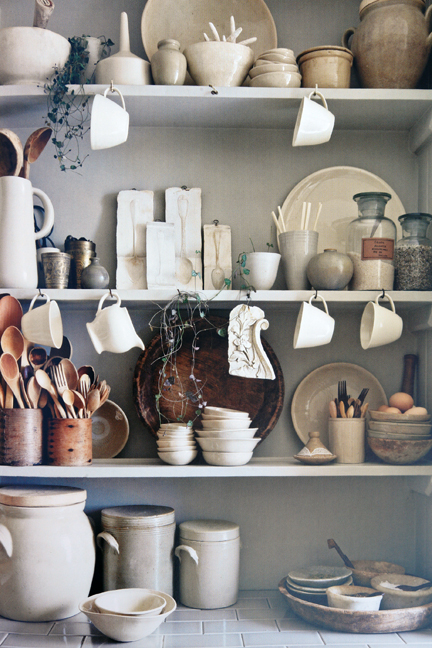 shelves covered in vintage cream coloured pottery, crockery and wooden utensils