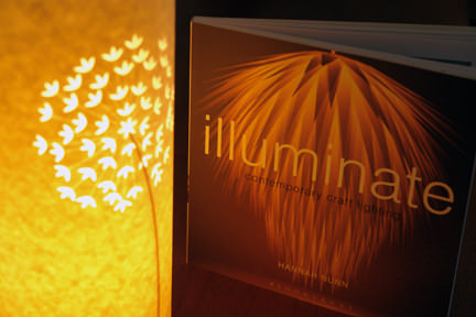 cover of Hannah Nunn's Illuminate: Contemporary Craft Lighting book beside one of her Allium paper cut lamps