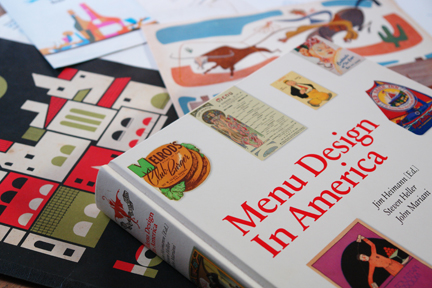 """Menu Design in America"" book surrounded by vintage menus"