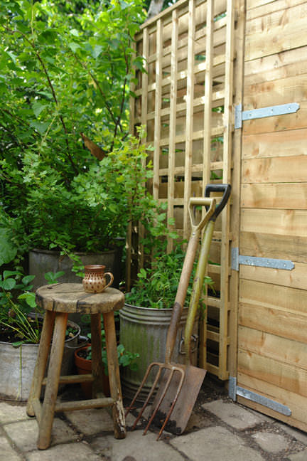 corner of our back garden showing a wooden stool and garden tools
