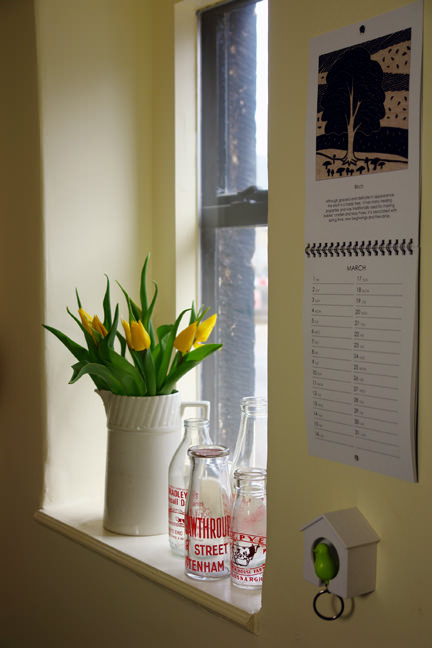 Gail Kelly's 2013 calendar hanging in our porch with white jug of yellow tulips and small vintage milk bottles