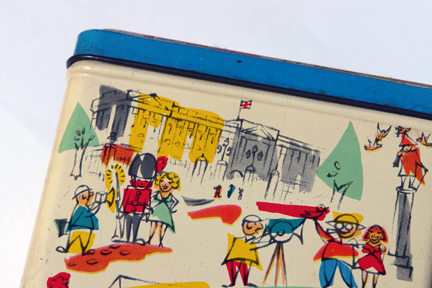 detail of the sides of vintage biscuit tin with cartoon-like illustrations of tourists at London sites such as Buckingham Palace and Trafalgar Square