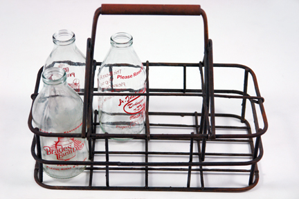 vintage metal milk carrier with vintage milk bottles