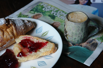 Croissant with mixed fruit jelly, small mug of cofffee & weekend newspaper