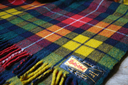 corner of a vintage Rally-Klad tartan travel rug