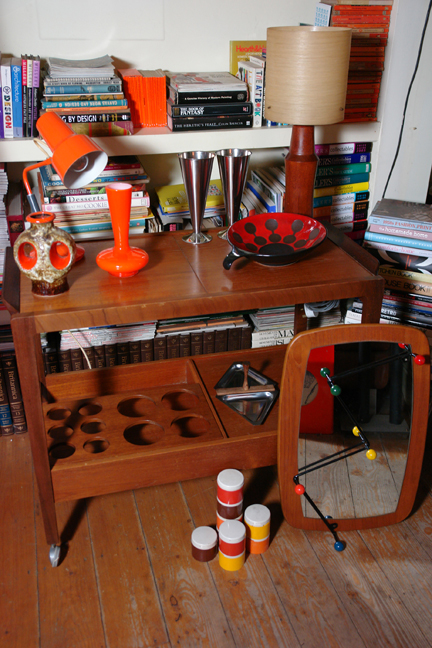 collection of midcentury modern and vintage items including West German pottery vase, Dumler and Breiden bowl, orange cased glass vase, orange desk lamp, teak lamp base with fibreglass shade, Scandinavian teak mirror, atomic coat rack, stacking Tupperware containers, stainless steel vases and snack tray and teak drinks trolley