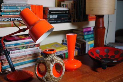 collection of midcentury modern and vintage items including West German pottery, orange cased glass vase, orange desk lamp, teak lamp base with fibreglass shade and teak drinks trolley